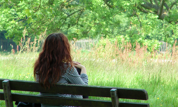 woman sitting on bench overlooking meadow