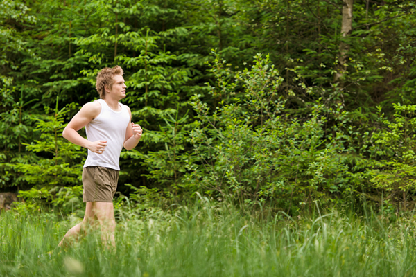 Young man jogging in forest.
